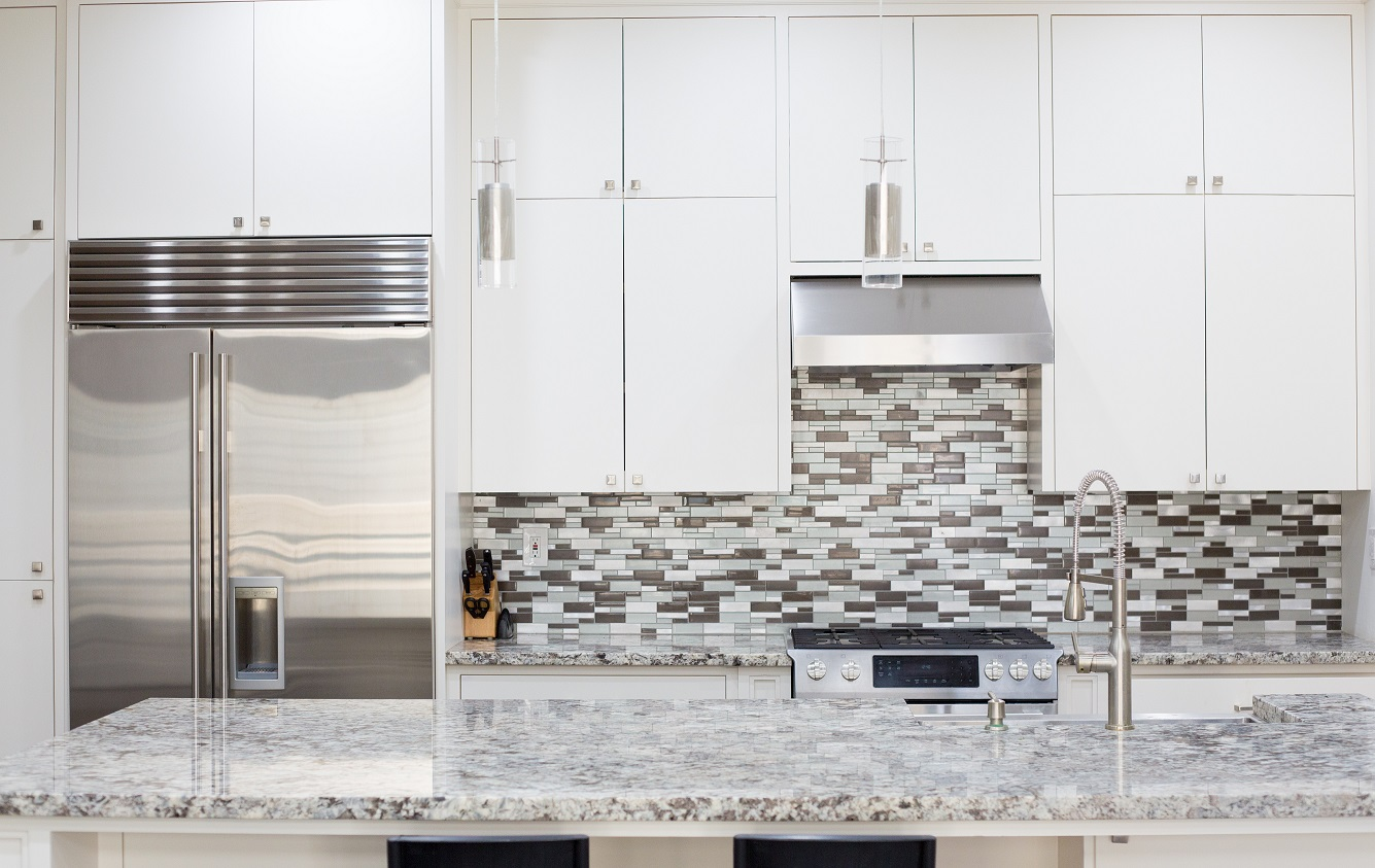gray kitchen with gray kitchen countertops and gray/blue patterned backsplash