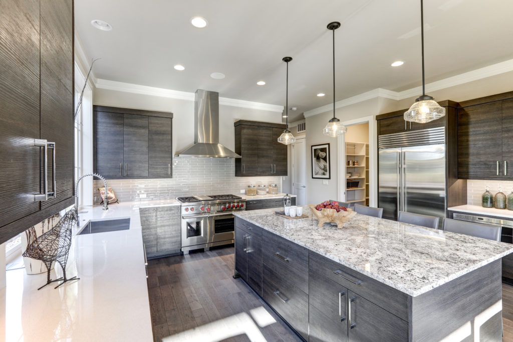 A beautiful kitchen with quartz counter-tops, overhead lighting, gray black wood cabinets, and stainless steel appliances sits idle.