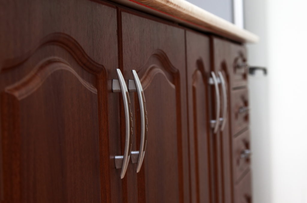 Close-up of brown wooden cabinets in home kitchen.