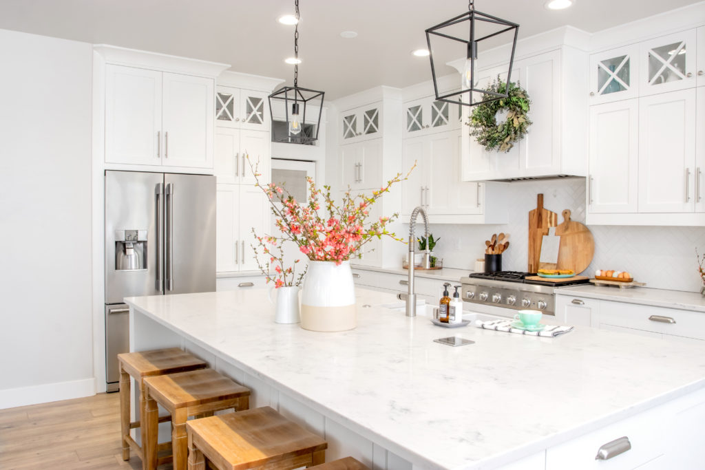 A big vase full of flowering branches in the on the countertop of a modern farmhouse kitchen.